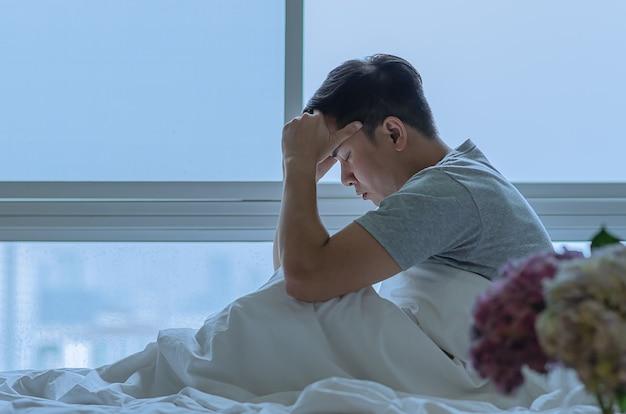 Een persoon zit en voelt zich depressief op bed depressie en eenzaamheid concept