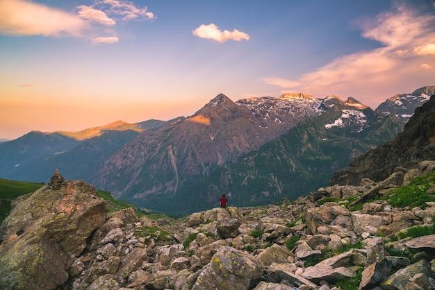 Een persoon zit op rotsachtig terrein en kijkt naar een kleurrijke zonsopgang hoog in de alpen.