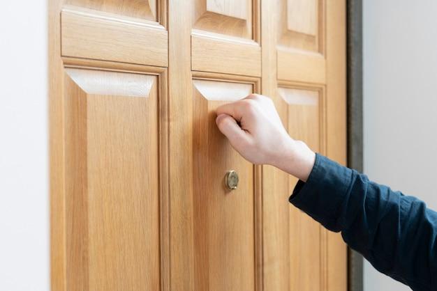 Een persoonshand klopt op de deur, bezoek het vriendenhuis