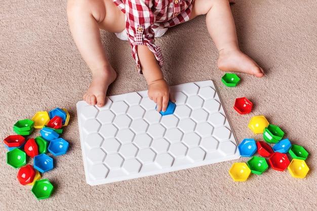 Een peuter speelt met een plastic mozaïek op het tapijt in de kinderkamer. vroege ontwikkeling, de montessori-methode.
