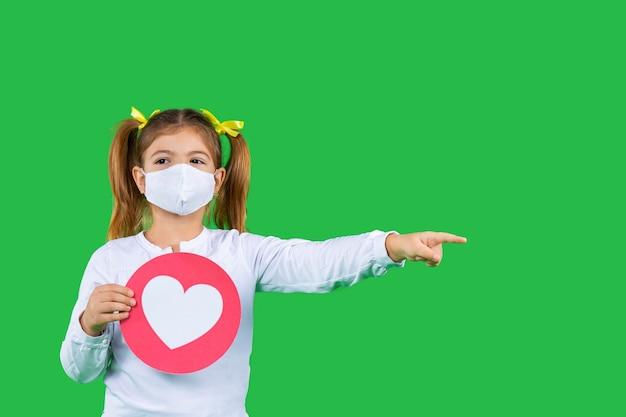 Een peutermeisje met een beschermend masker houdt een bord met een rood hart-emoticon vast en toont haar index