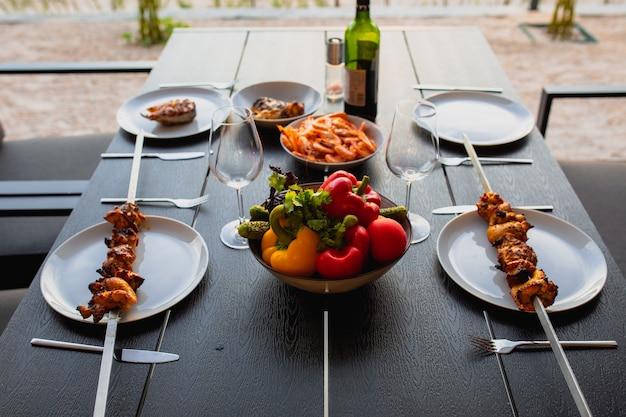 Een picknick op het terras voor vriendenterras met barbecue bij zonsonderganggebakken vlees op straat thuis kebabgegrild vlees wordt thuis geserveerdgegrild vlees met wijn en groentenzomer op het terras