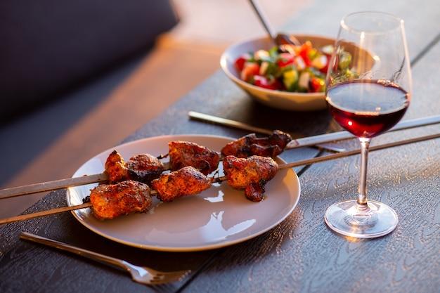 Een picknick op het terras voor vriendenterras met barbecue bij zonsonderganggebakken vlees op straat thuis