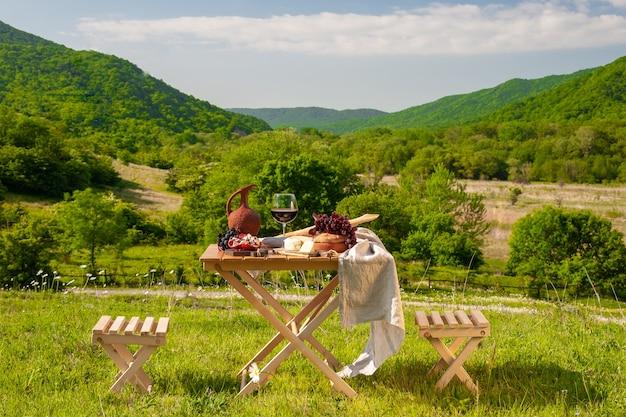 Een picknicktafel met rode wijn, kaas, fruit, druiven en brood staat in een weiland in groen gras