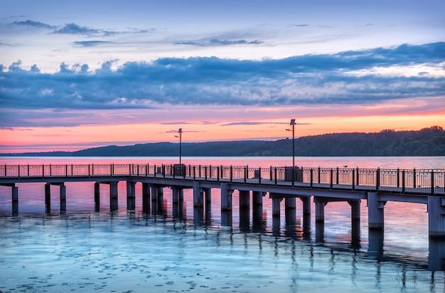 Een pier aan de wolga in de stad plyos onder een roze avondrood