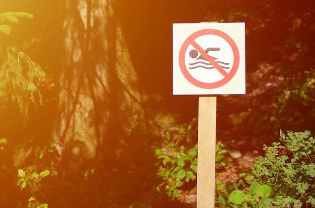 Een pijler met een bord dat een verbod op zwemmen aangeeft. het bord toont een doorgestreepte zwevende persoon