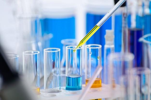 Een pipet die monster in een reageerbuis laat vallen, abstracte wetenschap