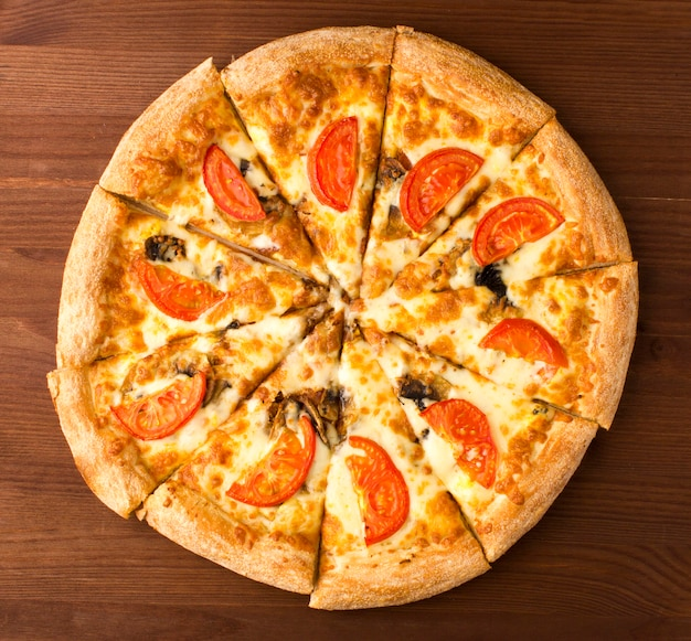 Een pizza met tomaten en champignons op een houten achtergrond