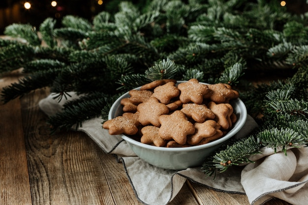 Een plaat met koekjes op een achtergrond van dennentakken.