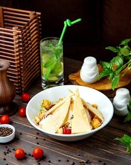 Een plaat van caesarsalade met kippenparmezaanse kersensla en broodvulling