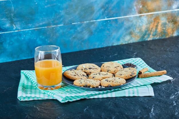 Een plaat van chocoladeschilferskoekjes en een glas jus d'orange op donkere lijst met kaneel