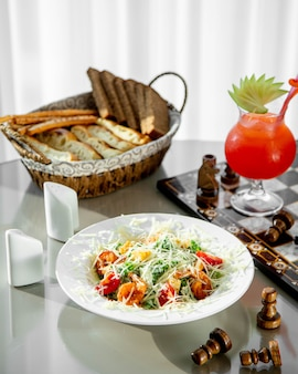 Een plaat van garnalen caesar salade geserveerd met broodmand en fruitcocktail