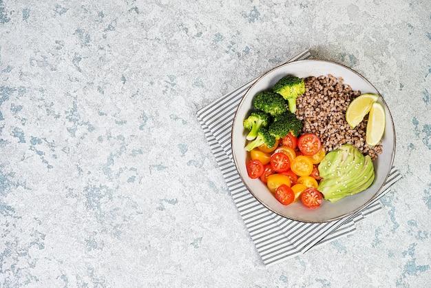 Een plaat van gezonde vegan salade voor de lunch op een grijze achtergrond.