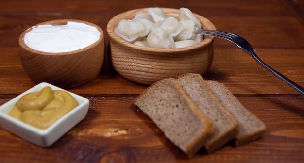 Een plaat van heerlijke gekookte dumplings op een donkere houten tafel met verschillende sauzen en brood