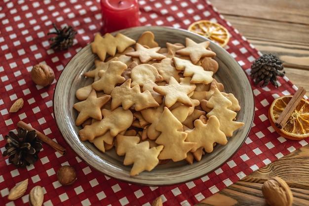 Een plaat van heerlijke zelfgemaakte vakantie vormige koekjes op een rood tafellaken op een houten tafel