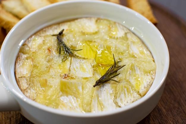 Een plaat van hete gebakken camembertkaas met rozemarijnclose-up