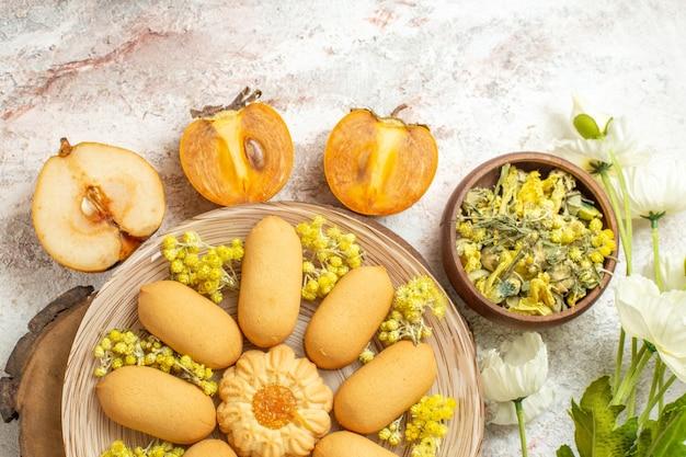 Een plaat van koekje op houten plaat en een kom met kruiden en fruit en witte bloemen op marmeren grond