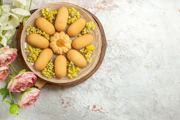 Een plaat van koekjes op houten schotel en bloemen aan de linkerkant van marmer
