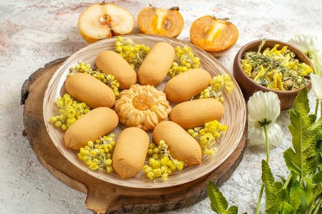 Een plaat van koekjes op houten schotel en een kom met kruiden en fruit en bloemen op marmeren grond