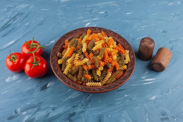 Een plaat van multi gekleurde ruwe spiraalvormige deegwaren met verse rode tomaten en kruiden.