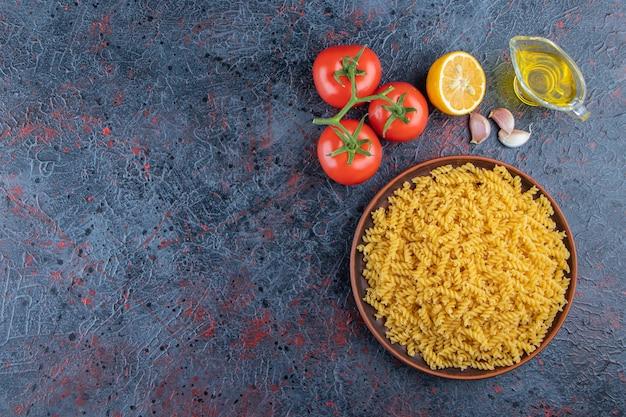 Een plaat van ongekookte spiraalvormige deegwaren met olie en verse rode tomaten op een donkere achtergrond.
