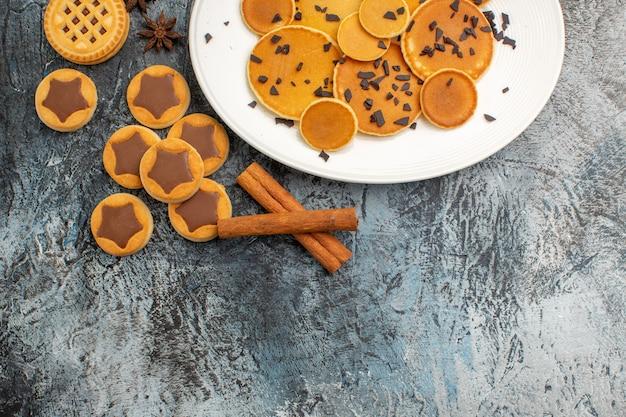 Een plaat van pannenkoek met koekjes en kaneelzieken op grijs