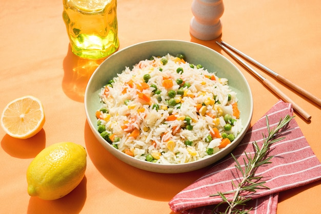 Een plaat van witte rijst met groenten op een stijlvolle trending oranje muur, hard zonlicht, aziatisch eten
