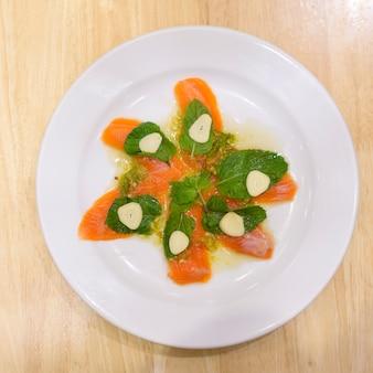 Een plaat van zalm met pittige zeevruchtensaus op houten tafel