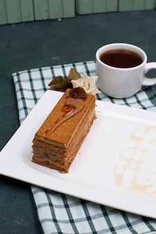 Een plak cake met karamelsaus en een kopje thee