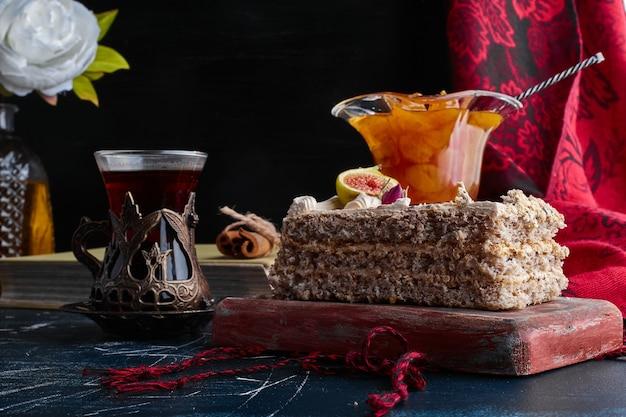 Een plak cake met kersenconfituur en een glas thee.