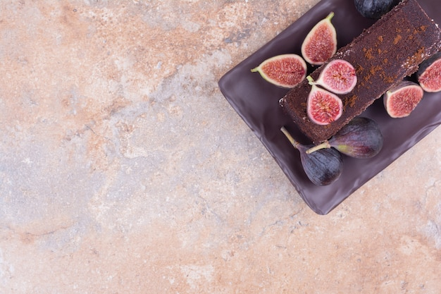 Een plak chocoladetaart in een zwarte schotel met vijgen.