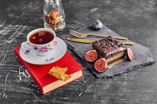 Een plak chocoladetaart met fruit en een kopje thee op een stenen schaal.