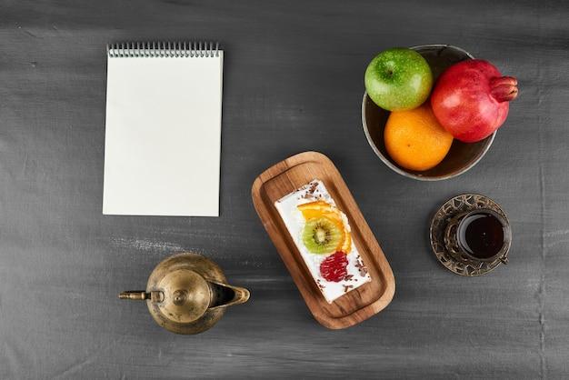 Een plak fruitcake met een receptenboek opzij.