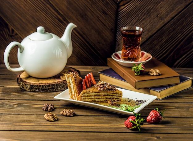 Een plak honingcake, medovik met een glas thee