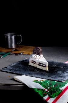 Een plak oreo cheesecake versierd met oreo koekjes en witte room