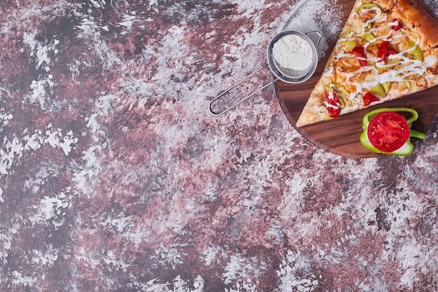 Een plak pizza geserveerd met groenten