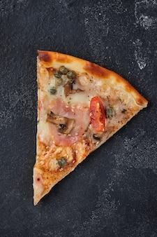 Een plak pizza met tomaten ham kappertjes champignons mozzarella kaas kruiden en tomatensaus