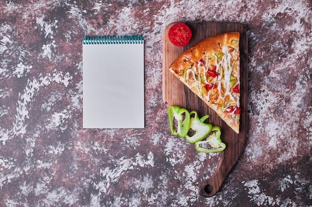 Een plak pizza op een houten bord met een receptenboek opzij op het marmer.