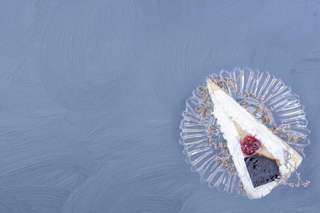 Een plak van cheesecake in een glazen schotel op blauwe achtergrond