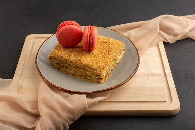 Een plak van de vooraanzichtcake lekker en gebakken binnenplaat met macarons op het houten bureau en het donkere suikergoed van het cakekoekje