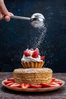 Een plak van de vooraanzichtcake met room en verse rode aardbeien binnen plaat die suikerpoeder op de donkere achtergrond krijgen