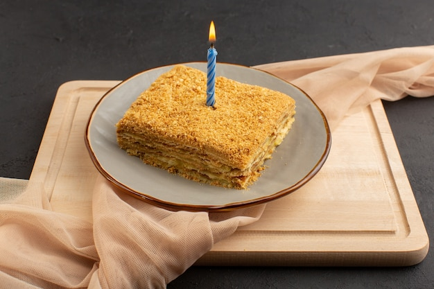 Een plak van de vooraanzichttaart lekker en gebakken binnenplaat op het houten bureau en het donkere suikergoed van het cakekoekje