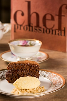 Een plak van rijke chocoladetaart met ijs en koffie op tafel