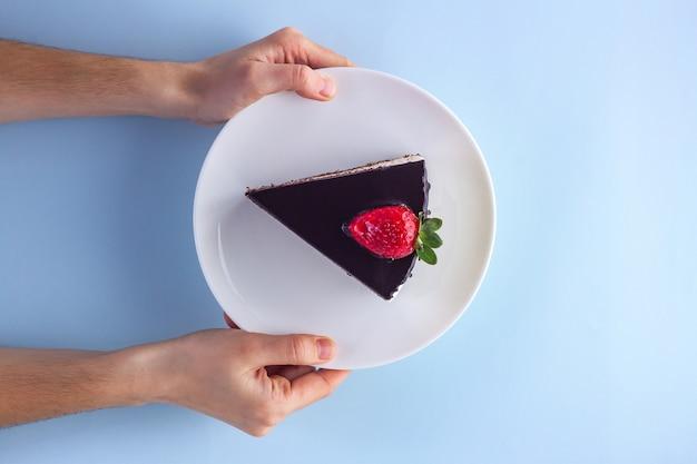 Een plak van zoete aardbeientaart met druipende chocoladeglans in een witte plaat in handen op blauw