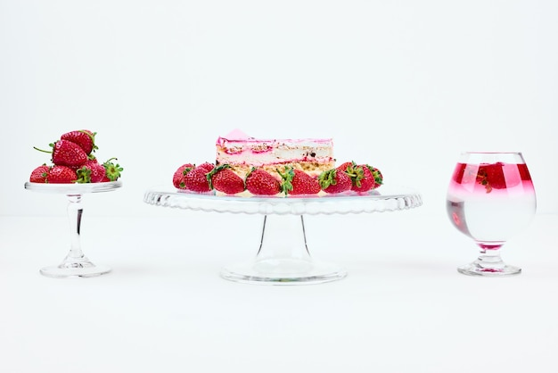 Een plakje aardbeiencheesecake met fruit en een glas drank.
