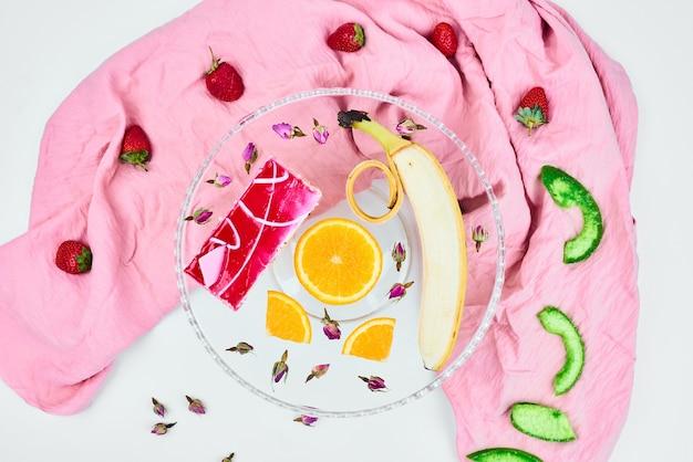 Een plakje aardbeienkaastaart met fruit eromheen.