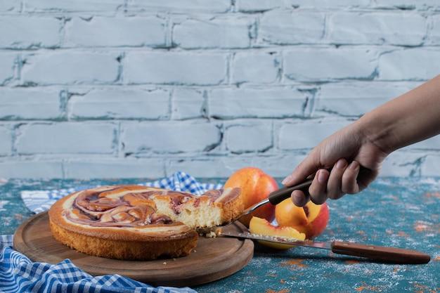 Een plakje aardbeientaart snijden op een houten bord.