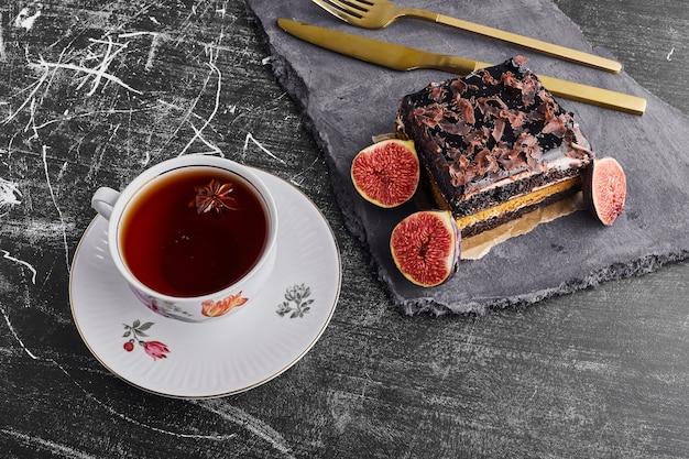 Een plakje brownie cake met vijgen en een kopje thee.
