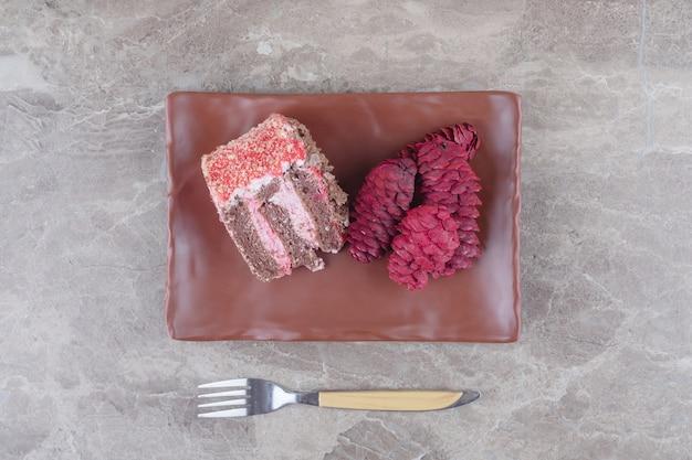 Een plakje cake en rode dennenappels op een schaal naast een vork op marmer