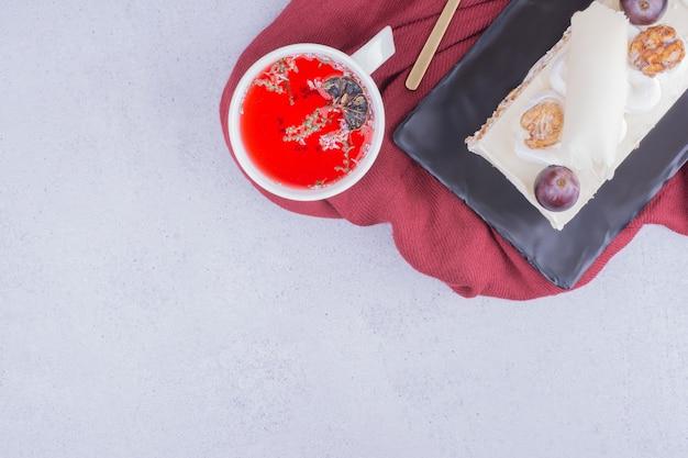 Een plakje cake in een keramische schotel met een kopje rode kruidenthee.